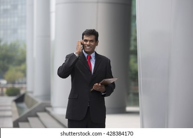 Indian businessman talking on his Smart phone outdoors in Asian city.