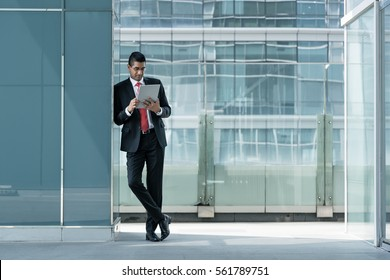 Indian businessman using a tablet PC while leaning on the wall of a modern office building indoors