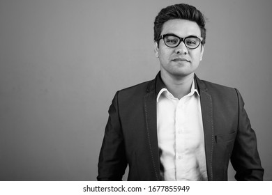 Indian businessman wearing suit against gray background