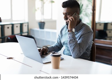 Indian businessman working on laptop and talking on the phone
