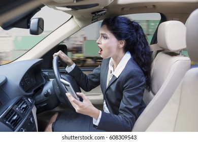 Indian businesswoman driving a car while using a mobile phone and looks shocked staring at the road