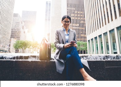 Indian businesswoman receiving text message on smartphone while sitting on bench outdoor in city. Young female browsing LTE internet and reading article on website. Millennial people communication