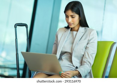 indian businesswoman using laptop while waiting for her flight