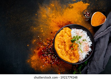 Indian butter chicken curry with basmati rice on dark background. Traditional homemade food concept. Top view, copy space
