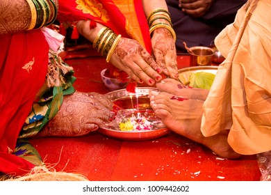 Indian candid wedding photography .Focus on hands , foot . colorful image . people are performed rituals .