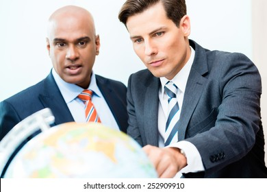 Indian and Caucasian business men discussing offshoring project looking at globe exploring new markets