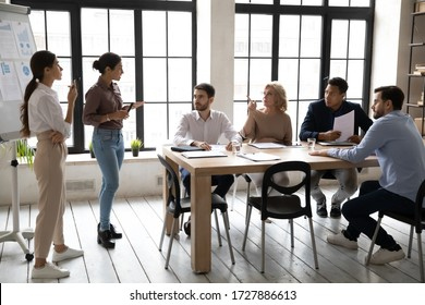 Indian and caucasian businesswomen flip charts presentation new project in boardroom at company meeting. Confident auditors speaks with mature and black partners about business using board and graphs.
