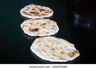 Indian chapatti on fire, Pushkar, India Close up. Fried tortillas on a hot baking sheet. Street food. Naan.