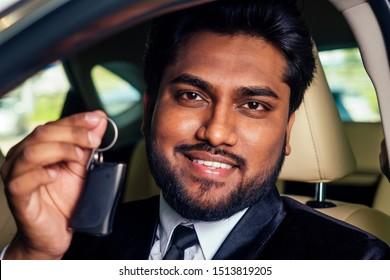 indian cheerful car salesman showing new keys showroom.