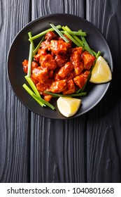 Indian chicken 65 with sauce and green onions and lemon close-up on a plate on the table. Vertical top view from above