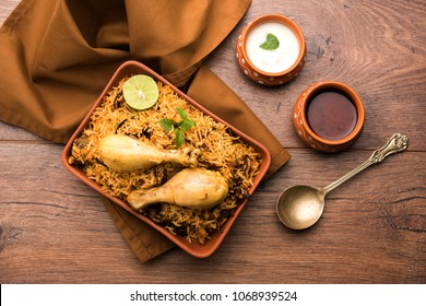 Indian Chicken Biryani served in a terracotta bowl with yogurt over white background. selective focus