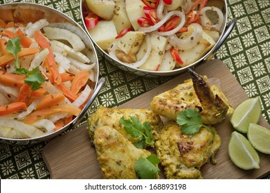 Indian chicken on a platter with bowls of salad and a garnish of lime, corriander and chili