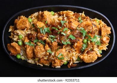 Indian chicken tikka biriyani in a cast iron sizzler dish