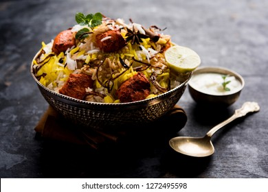 Indian Chicken Tikka Biriyani served in a bowl with yogurt. selective focus
