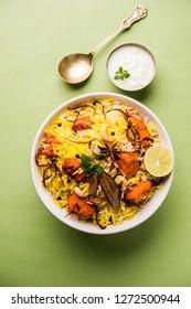 Indian Chicken Tikka Biriyani served in a bowl with yogurt. selective focus