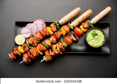 Indian chicken tikka kebabs, marinated in spices and yogurt and roasted in tandoor. served with green chutney and onion. selective focus