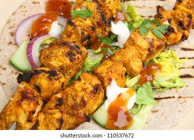 Indian chicken tikka kebabs served with chappati, salad and mango chutney.