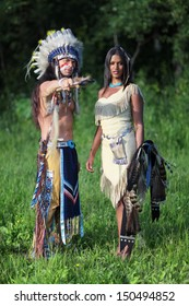 Indian chief with a young Indian on the green meadow