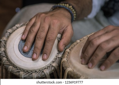 Indian classical drums - tabla - being played, with motion blur, beaded bracelet and copy space.