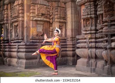 Indian classical odissi dancer at Brahmesvara Temple with sculptures in bhubaneswar, odisha, India