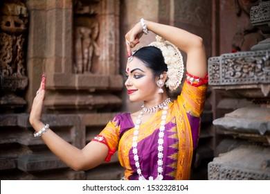 Indian classical Odissi dancer looks at the mirror during the Odissi dance recital against the backdrop of temple sculpture. Odissi dance or Orissi is a major ancient Indian classical dance form.