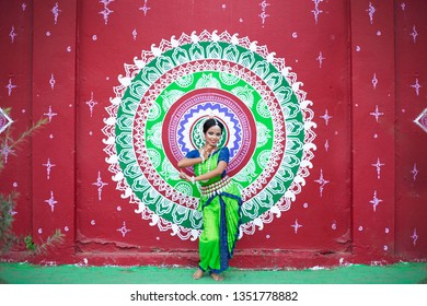 Indian classical odissi dancer posing infront of wall Street Art (Pattachitra) at Bhubaneswar, Odisha, India