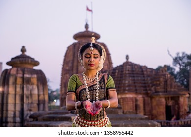 Indian classical odissi dancer striking pose against the backdrop of Mukteshvara Temple with sculptures in bhubaneswar, Odisha, India