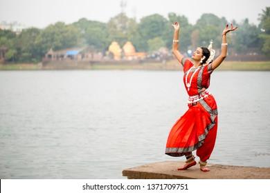 Indian classical odissi dancer striking pose at Bindu Sagar,  bhubaneswar, Odisha, India