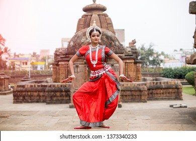 Indian classical odissi dancer striking pose at Mukteshvara Temple,Bhubaneswar, Odisha, India