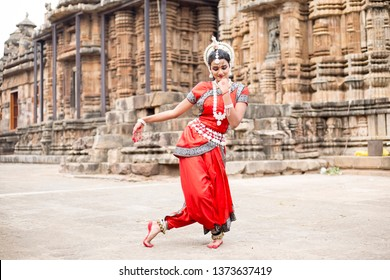 Indian classical odissi dancer striking pose against the backdrop of Ananta Basudeva temple with sculptures in bhubaneswar, Odisha.