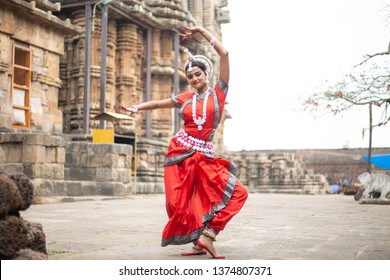 Indian classical odissi dancer striking pose at Ananta Basudeva temple with sculptures in bhubaneswar,odisha, India
