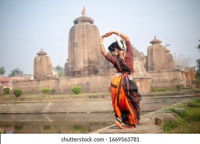 Indian classical odissi dancer striking a pose in front of Brahmeswara Temple, Bhubaneswar, Odisha, India