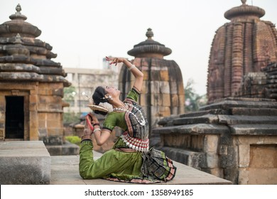 Indian classical odissi dancer wears traditional costume and posing in front of Mukteshvara Temple,Bhubaneswar, Odisha, India