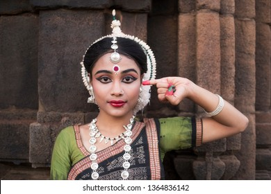 Indian classical odissi dancer wears traditional costume posing Mudra or Hand Gestures.