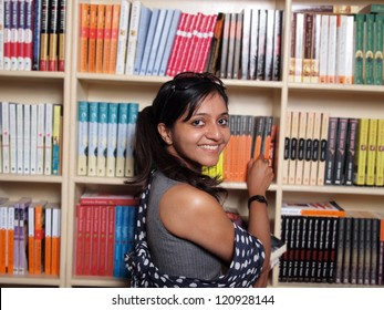 Indian college student selecting books in the campus library.