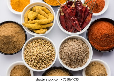 Indian colourful raw spices like red chilli (Mirch), Turmeric (Haldi), Coriander (Dhaniya) and Cumin (Jeera) powder. Served in bowls over white background. selective focus