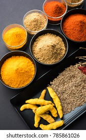 Indian colourful spices like Lal mirch, Haldi, Dhaniya and Jeera powder and whole. Served in bowl over black background. selective focus
