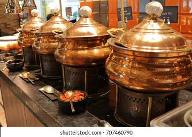 Indian copper pots with food at the Indian section of an international buffet table