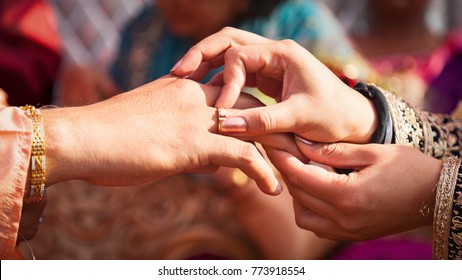 Indian couple exchanging their wedding rings during a Hindu Ring engagement ceremony.
