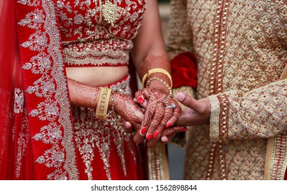 Indian Couple holding hands and bride showing mehndi design writh engagement rings