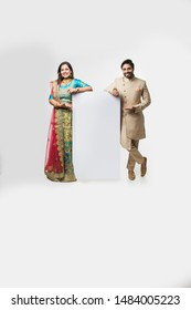 Indian couple holding white board, promoting offers on festival season while wearing traditional cloths, standing isolated over white background