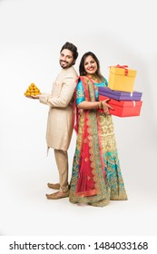 Indian couple with laddu and gift boxes on diwali /festival, standing isolated over white background. wearing traditional cloths