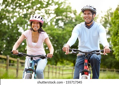 Indian Couple On Cycle Ride In Countryside