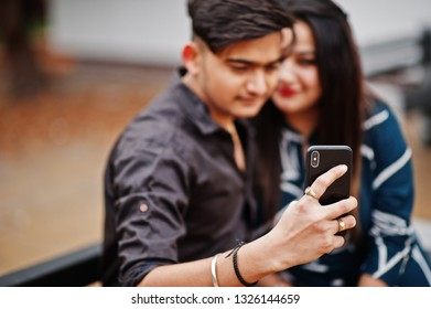 Indian couple posed outdoor, sitting on bench together and looking at mobile phone, making selfie.