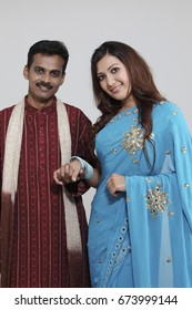 Indian couple posing at camera holding hand
