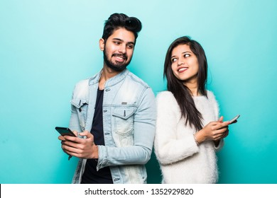Indian couple standing back to back and holding mobile phone isolated on green