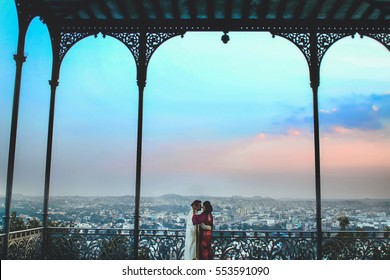 Indian couple stands on steel baclony under the archs with great cityscape behind