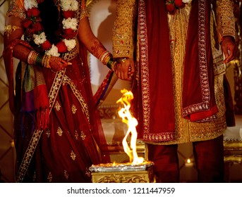 Indian couple walk seven steps reciting a prayer at each step of the sacred fire