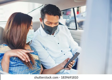 Indian couple wearing face medical masks taking a cab and using mobile phone app for booking