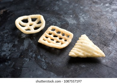 Indian crunchy fryums or papad snack in wheel, square and triangle shape. selective focus